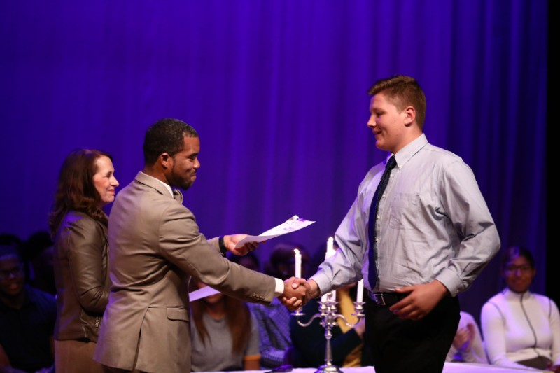 Principal Dr. Nigel A. Traylor and NHS Moderator/Faculty member, Mrs. Linda Corley, presenting certificates to new NHS student inductees.Shown here with Dr. Traylor, Brennan Wicks '20