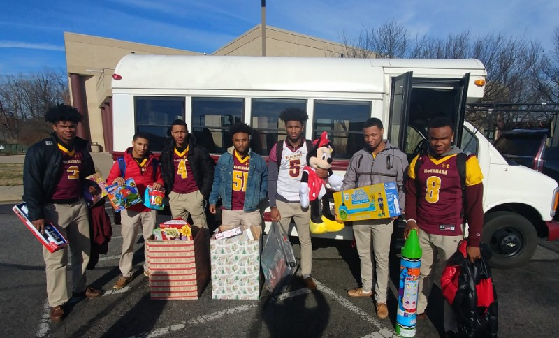 BMHS Football student athletes loading toys on the school bus to take to Children's Hospital Medical Center