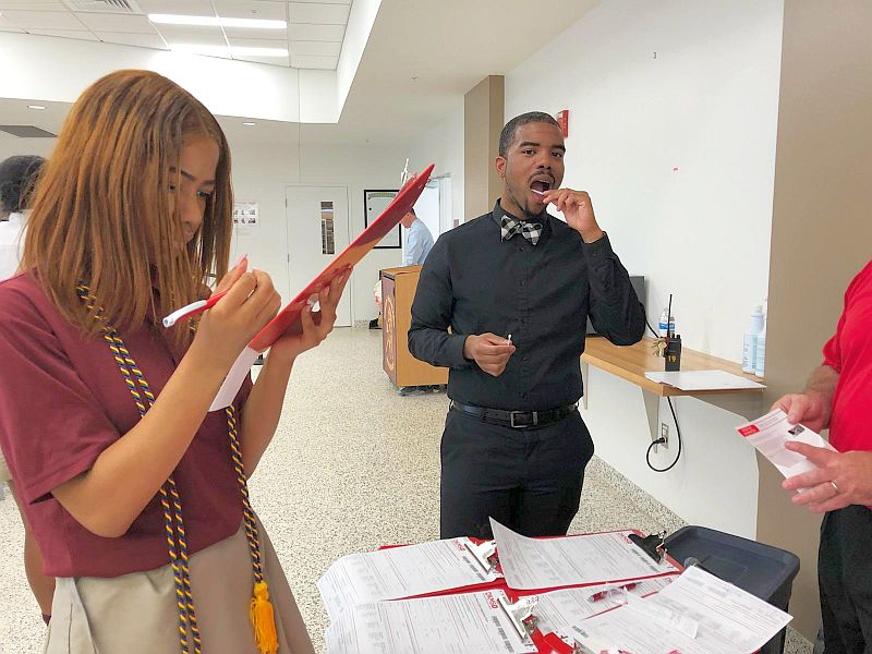 Dr. Nigel Traylor is swabbing and Class of 2018 Jalyn Sandiford takes time to register for the bone marrow registry